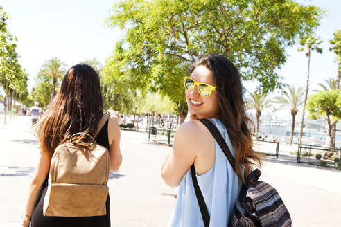 Spain, Barcelona, portrait of smiling woman with sunglasses having a walk with her best friend - VABF000654