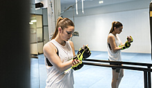 Young woman in gym putting on boxing gloves - MGOF002010