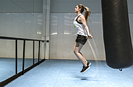 Young woman in gym skipping rope - MGOF002028