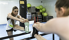 Young woman doing stretching exercises in gym - MGOF002034