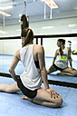 Young woman doing stretching exercises in gym - MGOF002037