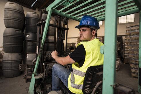 Worker inside cabin lift machine, barrels - JASF000895