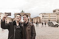 Two teenagers taking a smartphone image of themselves in front of the Brandenburg Gate in Berlin - MMFF001283
