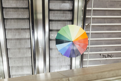Person with colorful umbrella going up on an escalator, high angle view - MMFF001286