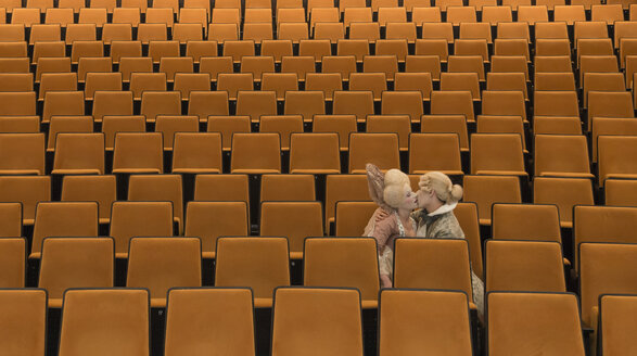 Kissing couple dressed in Baroque costumes sitting in an empty auditorium of a theatre - SKAF000022