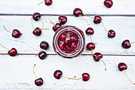 Open glass of homemade cherry groats and cherries on wood - LVF005072