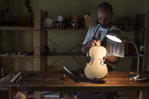 Luthier examining a violin in his workshop - ABZF000771