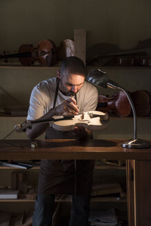 Luthier examining the sound post of an unvarnished violin in his workshop - ABZF000783