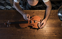 Luthier adjusting the sound post of a violin in his workshop - ABZF000789