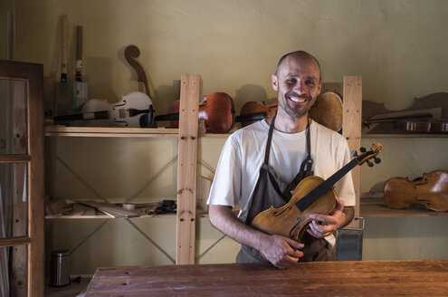 Smiling luthier holding a violin in his workshop - ABZF000792