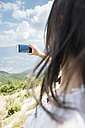 Greece, Central Macedonia, woman taking smartphone picture in the mountains - DEGF000872