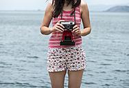 Greece, Amfilochia, woman with vintage camera  at the sea - DEGF000875