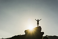 Silhouette of happy man standing on a rock at backlight - UUF007932