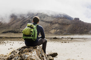 New Zealand, Tongariro National Park, back view of hiker with backpack looking to Tongariro Mountain - UUF007947
