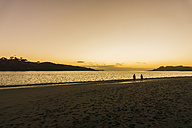 Two people walking on the beach at sunrise - UUF007953