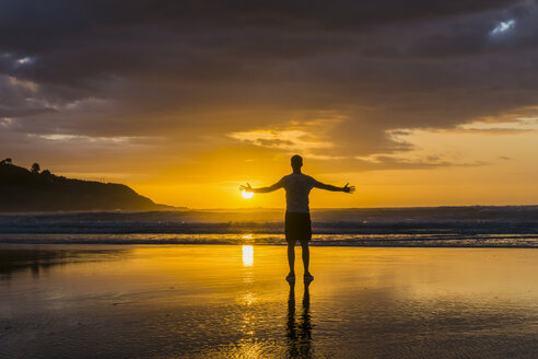 Silhouette of man standing on the beach with arms outstretched looking to the sea - UUF007959
