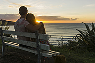 Couple in love sitting on bench looking at sunset - UUF007965