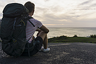 Back view of sitting hiker with backpack looking to the sea - UUF007968