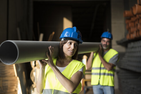 Construction workers carrying pipe in warehouse - JASF000938