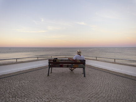 Portugal, Senior man siting on bench watching sunrise - LAF001659