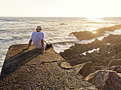 Portugal, Senior man sitting on wall at harbour at sunset - LAF001665