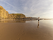 Portugal, Senior man standing at beach taking picture with digital tablet - LAF001671
