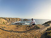 Portugal, Senior man mountain biking at the sea - LAF001680