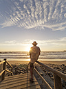 Portugal, Senior man sitting on railing at the beach - LAF001686