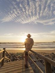 Portugal, Senior man sitting on railing at the beach - LAF001686