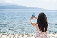 Greece, Sergoulas, woman taking pictures with smartphone at the coast - DEGF000886