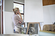 Woman observing canvas before setting up artwork at home studio - ZEF008880