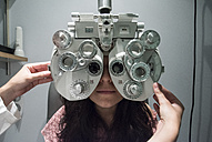 Ophthalmologist adjusting an optometrist phoropter, ready for eye calibration of a patient - ABZF000803