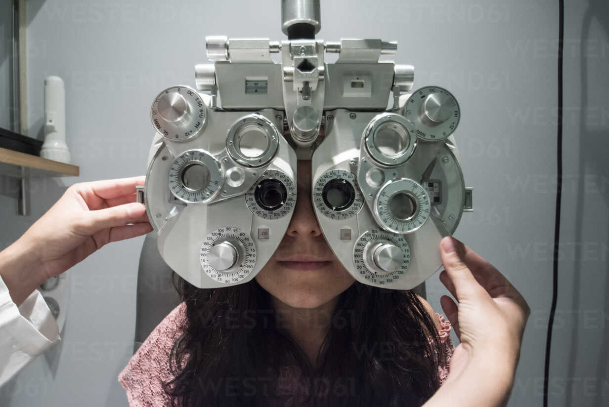Ophthalmologist adjusting an optometrist phoropter, ready for eye calibration of a patient - ABZF000803 - Andrés Benitez/Westend61
