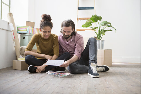 Couple sitting on floor of new flat choosing from color samples - RBF004591