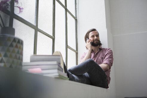 Man sitting on window sill talking on the phone - RBF004612