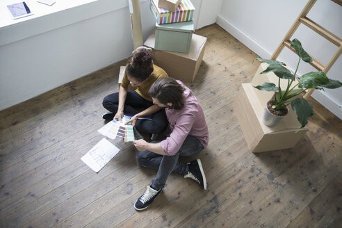 Couple sitting on floor of new flat choosing from color samples - RBF004672