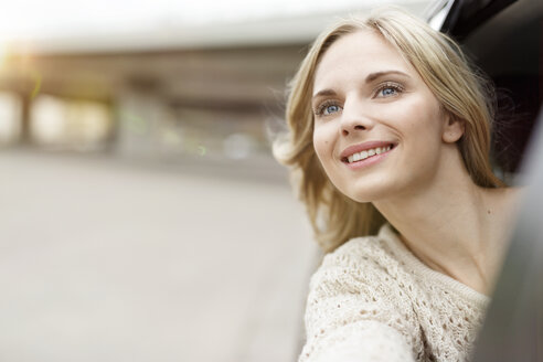Portrait of smiling young woman leaning out of car window watching something - PESF000186