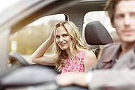 Portrait of smiling blond woman sitting on passenger seat in a car - PESF000189