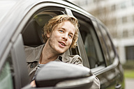 Portrait of smiling young man leaning out of car window watching something - PESF000192