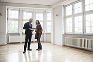 Real estate agent talking to client in empty apartment - RBF004679