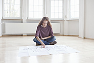 Woman looking at construction plan in empty apartment - RBF004682