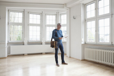 Man looking around in empty apartment - RBF004688