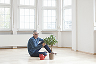 Man sitting on floor with plant in empty apartment - RBF004691