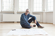 Portrait of smiling man with construction plan in empty apartment - RBF004694