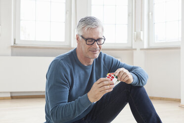 Man sitting on floor with Rubik's cube - RB004700
