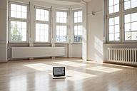 Laptop on floor in empty apartment - RBF004703