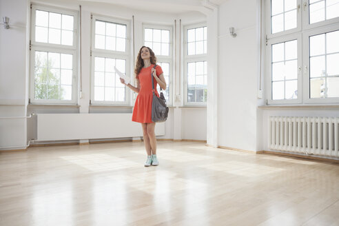 Woman looking around in empty apartment - RBF004706