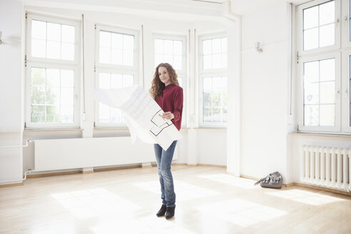 Woman holding construction plan in empty apartment - RBF004715