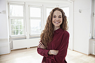 Portrait of smiling woman in empty apartment - RBF004718