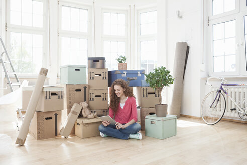 Woman surrounded by cardboard boxes using digital tablet - RBF004721